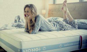 Frau liegt auf einer Hongi Matratze und lacht.